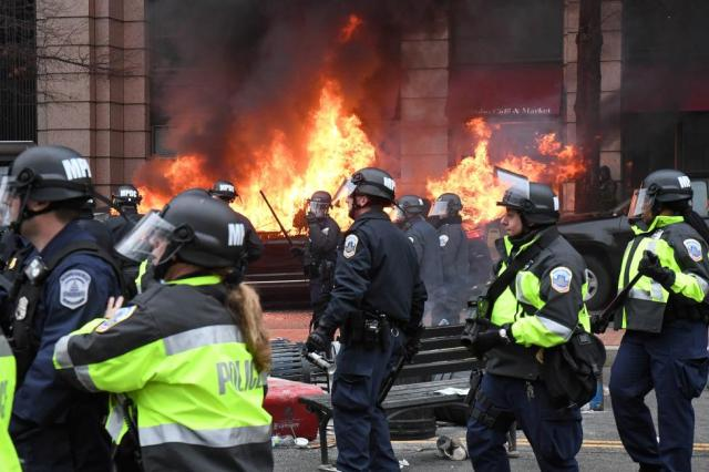 Police officers move protestors away from a car that was set on fire during protests near the inauguration of President Donald Trump in Washington
